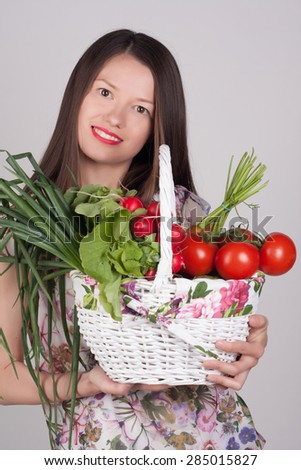 Close-up portrait of a young woman with a basket of fresh vegetables. Happy girl with carrots, reddish, onion and tomato. Vitamins and minerals. Healthy food concept. Grocery.