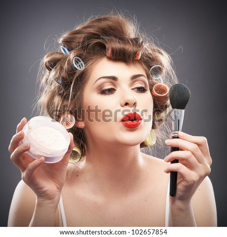 Close up portrait of a young woman with long hair on gray background making beauty face and hair style, applying powder at face. Smile happy girl  with make up accessories, studio isolated. - stock photo