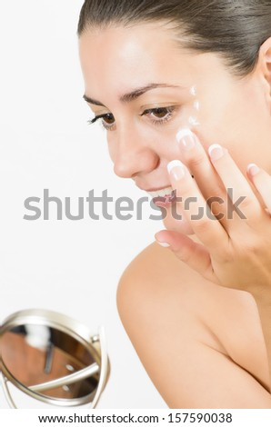 Close-up portrait of a young woman with perfect skin looking in the mirror - stock photo