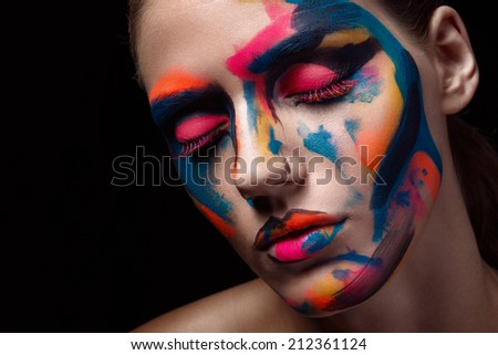 Close up portrait of a young woman with unusual makeup and closed eyes on a dark black background