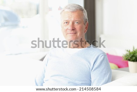 Close-up portrait of active old man sitting at sofa in nursing home.