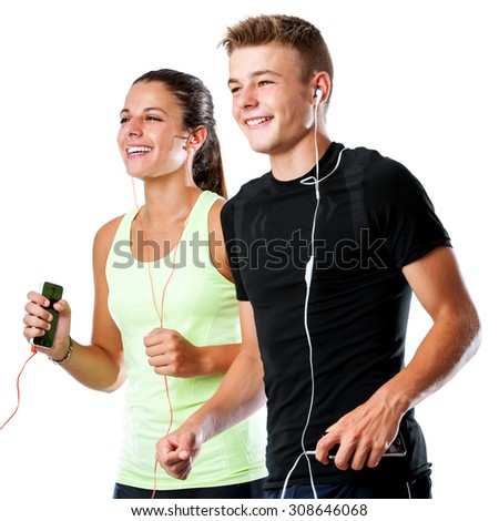 Close up portrait of active teen couple doing fitness workout together.Couple jogging together with smart phones and earphones isolated on white background. - stock photo
