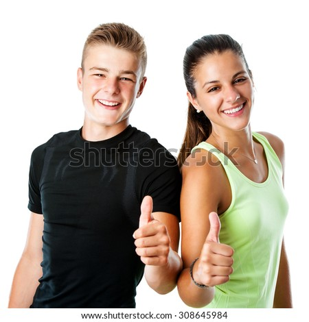 Close up portrait of active teen couple in sportswear doing thumbs up.Isolated on white background. - stock photo