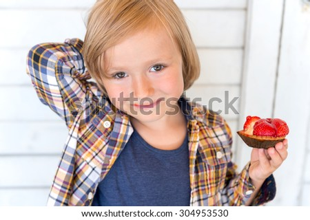 Close up portrait of adorable kid boy, standing against white wooden background, holding strawberry cake - stock photo