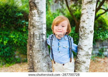 Close up portrait of adorable little blond boy, wearing pants with suspenders - stock photo