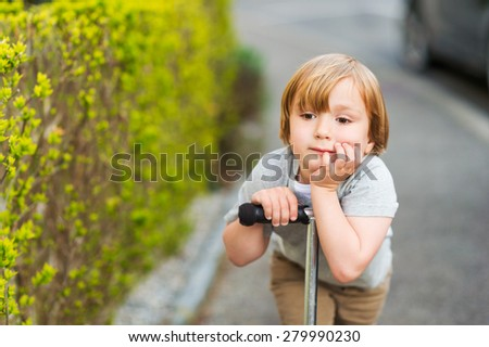 Close up portrait of adorable young 4 years old blond boy leaning on his scooter - stock photo