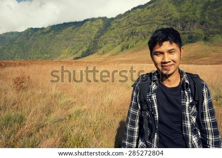 Close up portrait of adventure man on the mountains with smile - stock photo