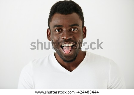 Close up portrait of African American student boy wearing white T-shirt making funny face, looking and showing tongue at the camera after classes at university. Attractive young male model having fun  - stock photo