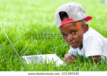 Close up portrait of African boy with baseball hat laying with laptop on grass.  - stock photo