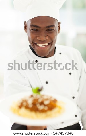 close up portrait of african chef in hotel kitchen presenting pasta - stock photo
