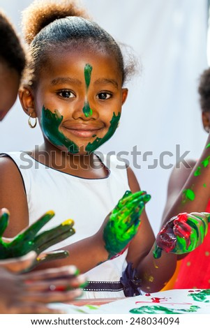 Close up Portrait of African girl painting with friends.Isolated against light background.  - stock photo