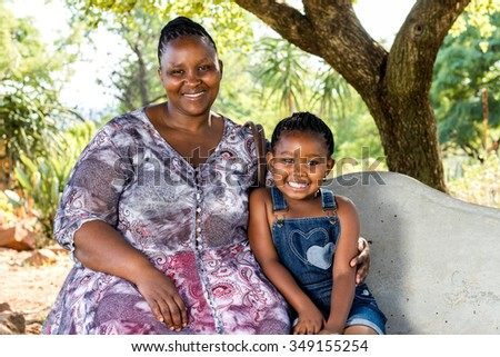 Close up portrait of african mother and child sitting on bench in park. - stock photo