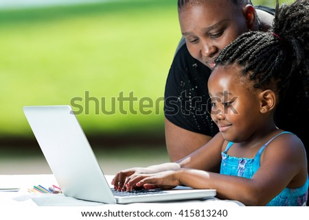Close up portrait of african mother supervising school work of little daughter on laptop. Cute girl typing on laptop against green background outdoors. - stock photo