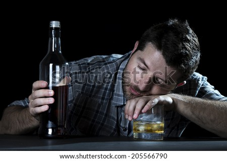 close up portrait of alcoholic wasted man sleeping drunk looking at whiskey glass avoiding temptation thinking of alcohol addiction , drinking abuse , alcoholism concept isolated on black background - stock photo