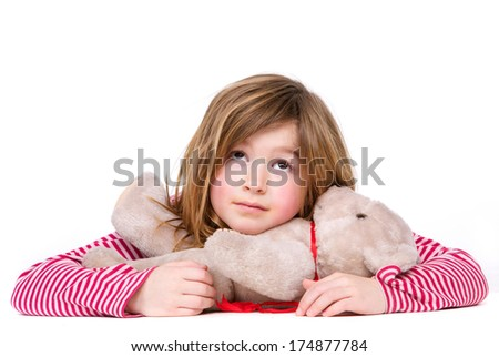 Close up portrait of an adorable young girl relaxing with teddy bear on isolated white background