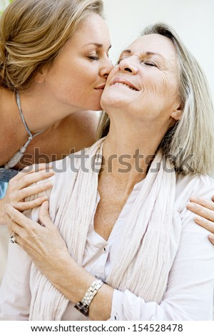 Close up portrait of an adult daughter kissing her mature mother on the cheek, being affectionate and smiling with joyful expressions while relaxing at home. - stock photo