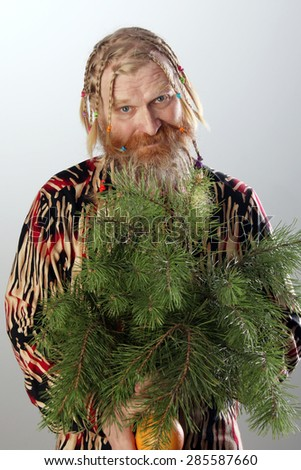 close-up portrait of an adult male with long beard, mustache and hair braided in pigtails holding a pine branch and orange studio on light background - stock photo