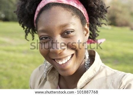 Close up portrait of an african american woman smiling happily at camera.