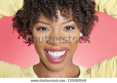 Close-up portrait of an African American woman smiling over colored background - stock photo