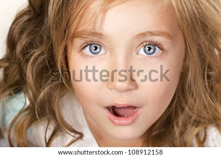 close-up portrait of an amazed little girl with blue eyes - stock photo
