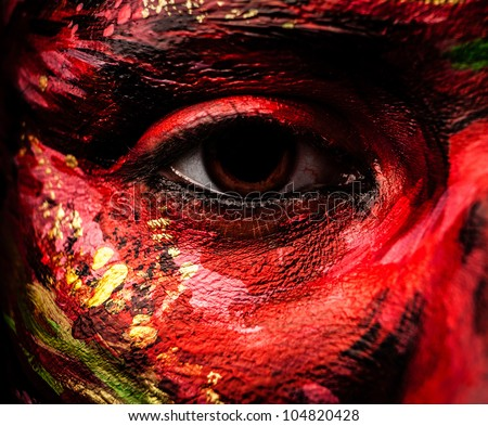 Close-up portrait of an artistic woman painted with red & green color. Part of face photo. - stock photo