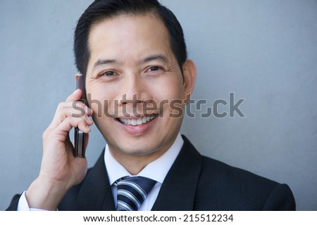 Close up portrait of an asian businessman smiling with mobile phone - stock photo