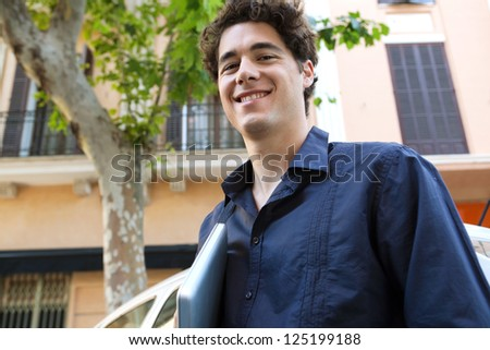 Close up portrait of an aspirational businessman wearing an elegant shirt and holding his laptop computer in the city, smiling. - stock photo
