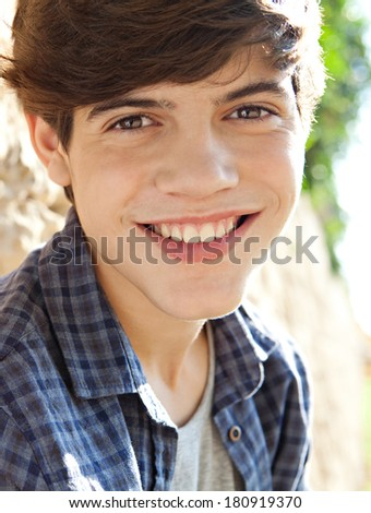 Close up portrait of an attractive and joyful teenager student boy leaning on an aged stone wall in a park during a sunny day, having fun and smiling at the camera, outdoors.