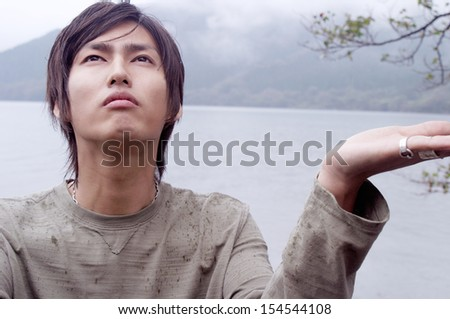 Close up portrait of an attractive asian japanese young man standing by a lake with mountains landscape holding his hand up to feel the rain during a rainy winter day outdoors. - stock photo