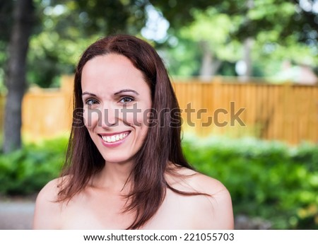 Close up portrait of an attractive brunette woman in her late 30's or early 40s outside in a park like setting on a sunny day during the summer season.  Room for copy space.