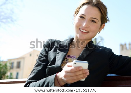 Close up portrait of an attractive business woman holding a smart phone while sitting down on a city park bench against a blue sky.