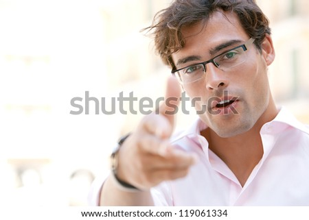 Close up portrait of an attractive businessman pointing at the camera with is fingers while standing next to office buildings in a classic city square. - stock photo