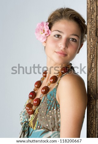 Close up portrait of an attractive exotic young woman wearing tropical clothes and standing next to a wooden screen panel at a health spa, smiling.