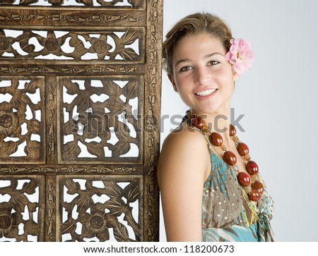 Close up portrait of an attractive exotic young woman wearing tropical clothes and standing next to a carved wood screen panel.