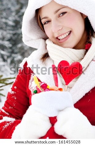 Close up portrait of an attractive girl holding a Christmas stocking full of candy sweets and joyfully smiling in the snow mountains on vacation, smiling outdoors.
