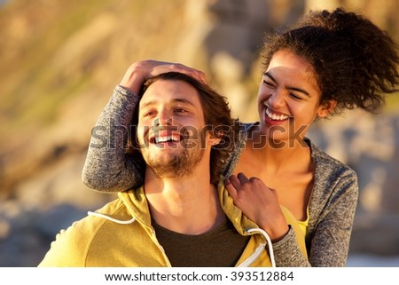 Close up portrait of an attractive modern couple laughing together - stock photo