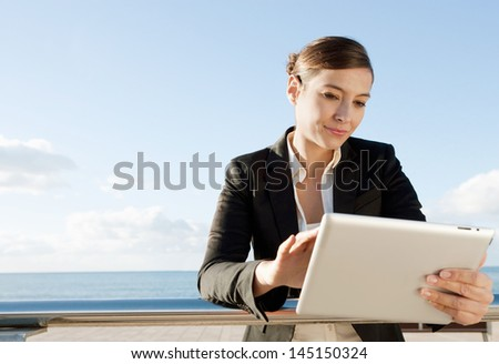 Close up portrait of an attractive professional business woman holding and using a digital tablet device and touching the screen while wearing a suit against a bright blue sky background. - stock photo