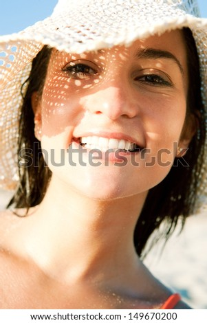 Close up portrait of an attractive smiling woman on vacation on a beach, wearing a straw hat and shading her face with it creating a sun pattern on her skin. Protecting from sun rays. - stock photo