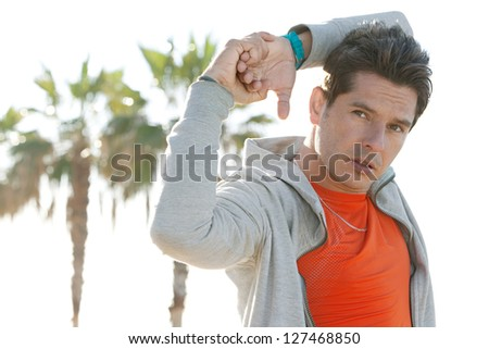 Close up portrait of an attractive sports man stretching his arms and exercising against a clean sky background with palm trees aligned in the background. - stock photo