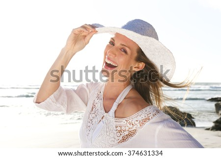 Close up portrait of an attractive woman laughing with hat at the beach  - stock photo