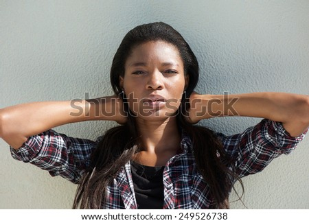 Close up portrait of an attractive young african american woman with hand in hair - stock photo