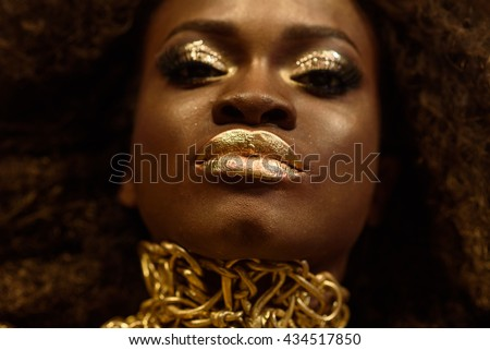 Close up portrait of an attractive young African woman with unique golden makeup - stock photo