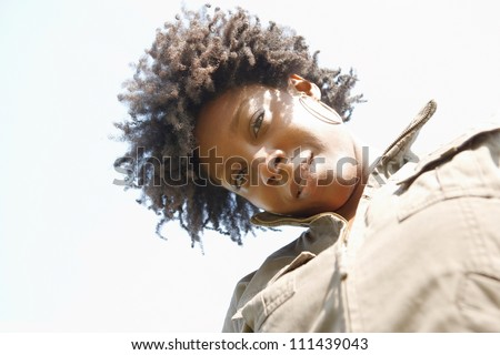 Close up portrait of an attractive young black woman against a blue sky.