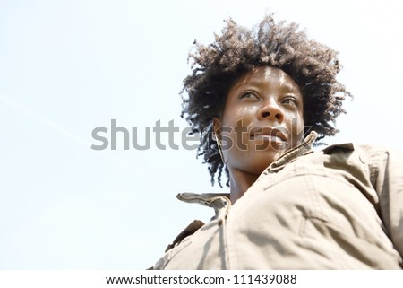 Close up portrait of an attractive young black woman against a blue sky, smiling. - stock photo