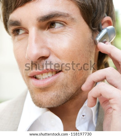Close up portrait of an attractive young businessman using a hands free ear piece device to make a phone call while in a classic city financial district, outdoors. - stock photo