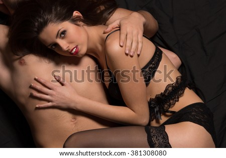 Close-up portrait of an attractive young couple resting all together. Beautiful woman in lingerie lying on naked man. - stock photo