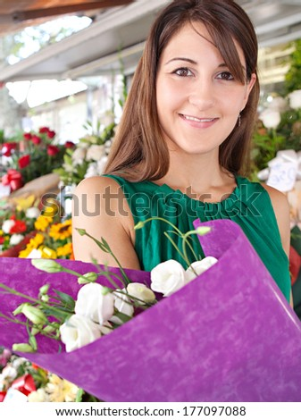 Close up portrait of an attractive young customer woman buying a bouquet of fresh flowers while visiting a florist market stall in a city street during a sunny day. Outdoors lifestyle shopping. - stock photo