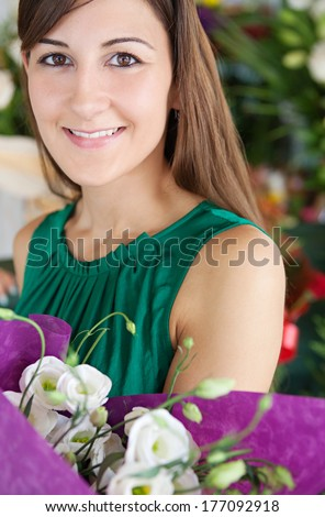 Close up portrait of an attractive young customer woman buying and holding a bouquet of white fresh flowers while visiting a florist market stall. Outdoors lifestyle shopping. - stock photo