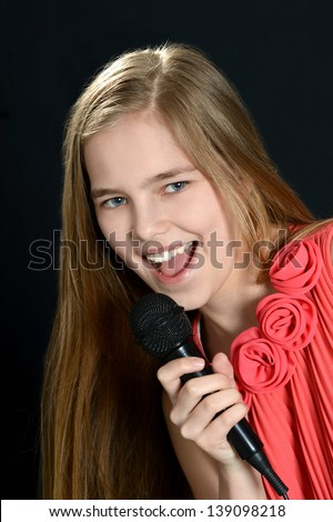 close-up portrait of an attractive young girl singing on a black background - stock photo