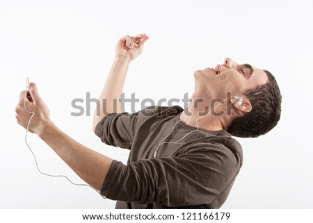 Close up portrait of an attractive young man listening and dancing to music with his headphones, isolated against a white background.